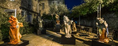 Gothic monster sculptures in summer cafe garden, night view. Carcassonne, France Stock Photo