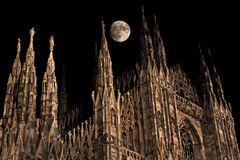 Gothic moonrise. Full moon over Milan gothic cathedral pinnacles stock photography