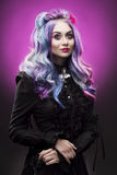 The gothic multi-colored hair girl on a violet background stock photography