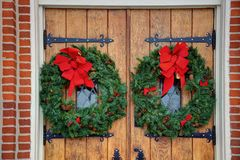 Church doors with wreaths. Gothic oak wooden church doors with ornate metal hardware, wreaths hung for Christmas, and red bow royalty free stock images