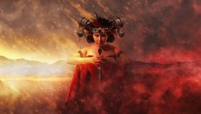 Gothic queen in red dress doing magic Royalty Free Stock Photos