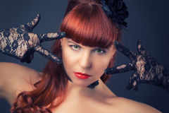 Gothic redhead woman in sexy black satin corset against dark gre Royalty Free Stock Image