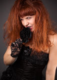 Gothic redhead woman in sexy black satin corset against dark gre Royalty Free Stock Photos