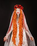Gothic redhead woman vampire in flower wreath with pale skin and red lips. Vampire from nightmare with long hair. Gothic witch in stock photography