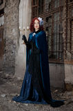 Gothic redhead woman walking with candle. Gothic redhead woman in cyan dress walking with candles Royalty Free Stock Images