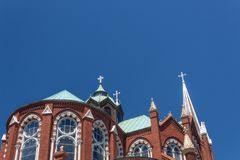 Gothic Revival church with beautiful windows, dome, and spire against a blue sky. Horizontal aspect royalty free stock photography