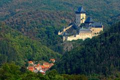 Gothic royal castle Karlstejn in green forest during autumn, Central Bohemia, Czech republic, Europe. State caste in with village Stock Photos