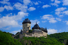 Gothic royal castle Karlstejn in green forest during summer with blue sky and white clouds, Central Bohemia, Czech republic, Europ Stock Photos