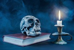 Gothic skull on old book and candle in candlestick on dark and smoked background Royalty Free Stock Images