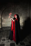 Gothic sorceress. Red sorceress with black cape and red smoke stock photo