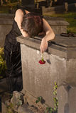 Gothic sorrow. Crying gothic girl leaning on a tombstone holding a rose Royalty Free Stock Photos