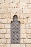 Gothic Stained Glass. Vertical view of an ancient gothic stained glass window and a granite block wall. Belongs to the Bishop's Palace. Located in Astorga, Spain Royalty Free Stock Image