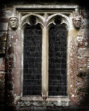 Gothic Stone Faces Next To A Church Window Stock Image