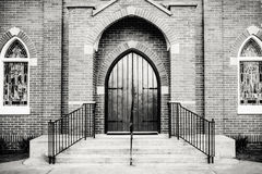 Gothic-style Front Entrance of a Church. Black and white photo of a Gothic-style wooden front door, entrance, and windows of a brick church Royalty Free Stock Photo