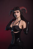 Gothic style girl with horns wearing corset and gloves Royalty Free Stock Image