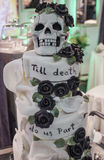 Gothic wedding cake. With black roses and a skull. With the inscription: Till death do us part Stock Photos