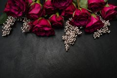 Gothic wedding flowers burgundy roses arrangement. Gothic wedding flowers decor. Dark red or burgundy roses with silver adornment on black background. Bold stock images
