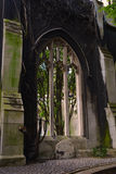 Gothic window in the black wall and the gravestone under it Stock Photography