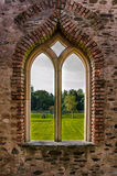 Gothic window overlooking gardens. Royalty Free Stock Photo