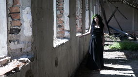 Gothic witch girl walking beside ruined windows in an old destroyed mansion. Contemplative gothic witch girl walking beside ruined windows in an old destroyed stock footage