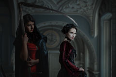 Gothic woman close to death. Mysterious women in gothic dress, standing next to the death with a scythe Stock Photography