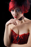 Gothic woman in corset. Red-headed gothic woman in black and red corset isolated on black Stock Images