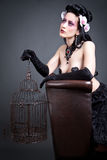Gothic Woman with a empty birdcage. Picture of a gothic woman with a empty birdcage Royalty Free Stock Images