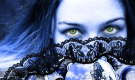 Gothic woman with fan and beautiful green eyes. Gothic woman with mysterious green eyes Royalty Free Stock Photography