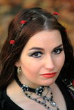 Gothic woman looking up portrait. Brunette gothic girl with red roses in her hair , brown eye's and red lipstick looking up into the camera stock image