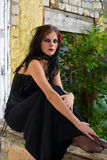 Gothic woman on windowsill. Woman dressed in gothic clothing sitting on windowsill looking serious Royalty Free Stock Photography