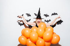 Gothic young woman in witch hat standing behind orange balloons stock image
