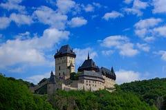 Gotisch koninklijk kasteel Karlstejn in groen bos tijdens de zomer met blauwe hemel en witte wolken, Centrale Bohemen, Tsjechisch Stock Foto's