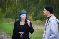 Gotische der Paare Liebesgeschichte draußen Mann und blaues Haarmädchen an der schwarzen Kleidung bei Green River Stockfotografie