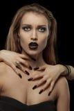 Gotische donkerbruine vrouw met handen op hals Stock Foto's