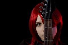 Gotisches Mädchen, das furchtsame Objektive mit Gitarre trägt Lizenzfreie Stockfotografie