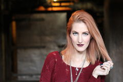 Gotisches Mädchen des schönen einsamen roten Hauptingwers nahe dunklem furchtsamem Tunnel Stockfotografie