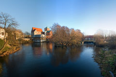 Gotisches Schloss durch einen Fluss. Stockbilder