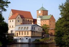 Gotisches Schloss durch einen Fluss. Stockfotografie