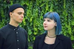Gotisk för par kärlekshistoria utomhus Man och slösa hårflickan på svart kläder på Green River Arkivbilder