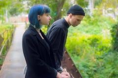 Gotisk för par kärlekshistoria utomhus Man och slösa hårflickan på svart kläder på Green River Arkivfoto