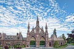 Gotisk ingång på grönskande skogkyrkogården royaltyfria bilder