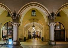 Gotiska gallerier av torkduken Hall på huvudsaklig marknadsfyrkant i Krakow vid natt Arkivbild
