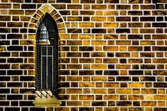 Gotiskt fönster i den orange tegelstenväggen Royaltyfria Bilder