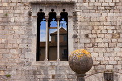 Gotiskt fönster på den forntida stenväggen med refle Royaltyfri Fotografi