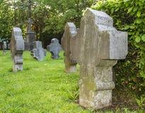 Gotiskt kors och gravvalv i kyrkogård på denHubert kyrkan, Aubel Royaltyfri Bild