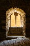 Gotiskt slottfönstersolljus som häller i mörk kontrastarkitekt royaltyfri bild