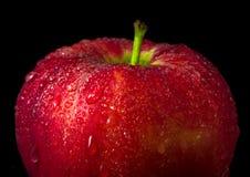 Gotita de agua en superficie brillante de la manzana roja en fondo negro Imagen de archivo