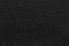 Gotitas de agua en negro Fotos de archivo libres de regalías