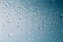 Gotitas de agua sobre el vidrio o la ventana con el fondo azul, descensos de la superficie líquida, macro Fotografía de archivo libre de regalías