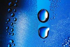 Gotitas de agua sobre un fondo azul Imagen de archivo libre de regalías